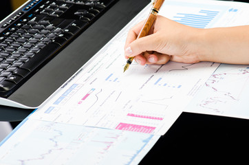 Woman's hands working on business reports at office