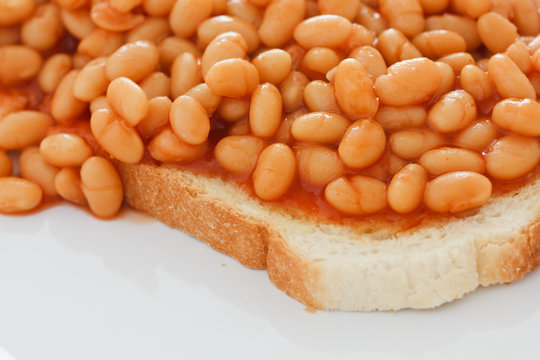 Detail of baked beans on white toast.
