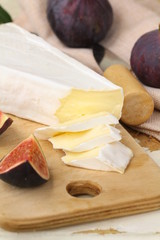 Brie cheese and sweet fruit  figs on a wooden board