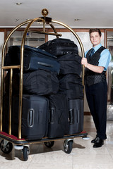 Concierge with a pile of bags in luggage cart