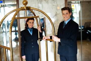 Concierges holding the cart and posing