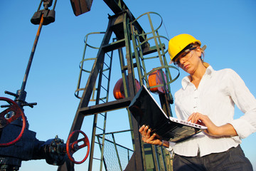 Businesswoman with a notebook in an oilfield