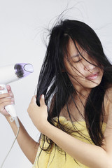 Portrait of beautiful asian woman, she holding hair dryer