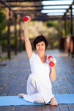 beautiful middle aged woman exercise with dumbbells