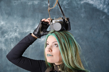 Steampunk-styled girl experiments with old fashion camera