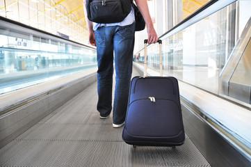 Traveler with a bag on the speedwalk .