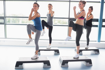 Four women raising their legs while doing aerobics