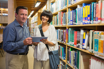 Mand and woman standing in the library holding a tablet pc