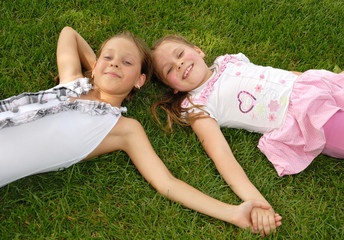 Two girls lie on green grass