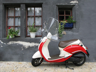 Trendy moped against old house. Fribourg, Switzerland