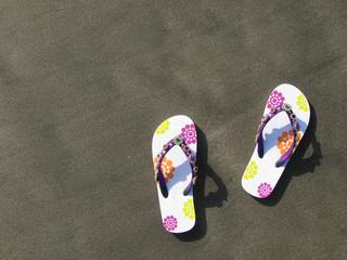 Flip-flops and hat on the black sand of Tenerife island, Canari