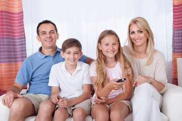 Happy Family On A Sofa Watching Tv