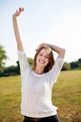 Young happy woman with raised arms