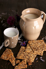 Pitcher and cup of milk with cookies on wooden table close-up