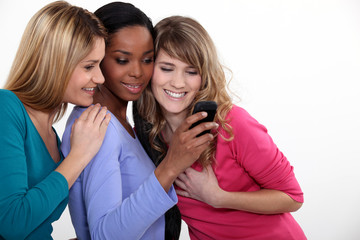 Girlfriends looking at a mobile phone