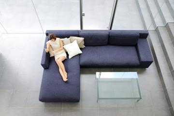 タブレットを持ってソファでくつろぐ女性