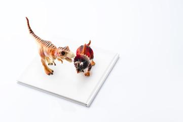 白色の本と恐竜の玩具