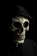 Hooded scary skeleton on black background