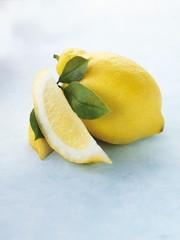 Whole lemon, lemon wedge and leaves