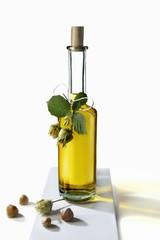 Oil in bottle with fresh hazelnuts