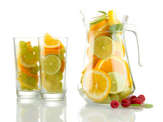 transparent jar and glasses with citrus fruits and raspberries,