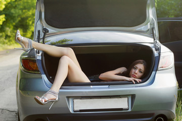 young woman in the trunk of car