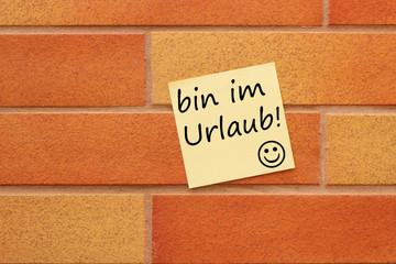 Wand mit gelben Zettel und Text bin im Urlaub