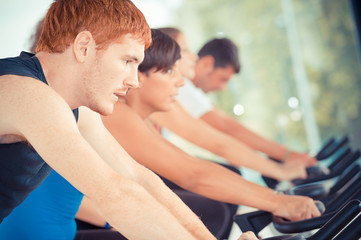 Group of five people in the gym, exercising their legs doing car
