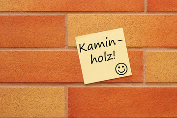Wand mit einem gelben Zettel Kaminholz