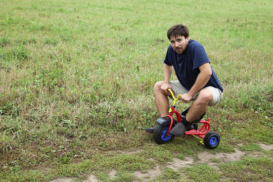 Adult man on a small tricycle