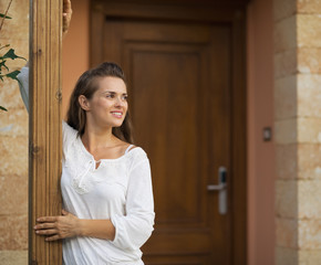 Happy woman standing on doorstep and looking on copy space