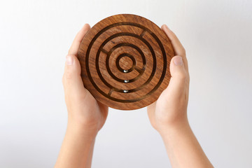Hands playing with wooden round maze toy on white background