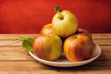 Fresh red apples on wooden tabletop against grunge red wall