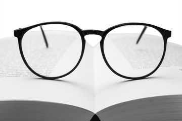 glasses on a book isolated on white