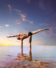 Man doing yoga exercise standing into the water