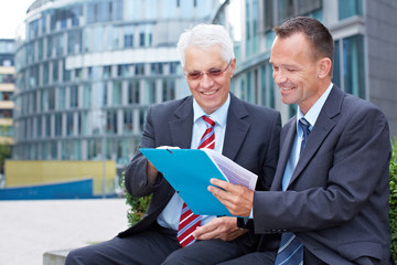 Geschäftsleute lesen Vertrag im Freien