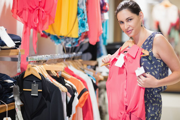 Woman in clothes store looking at shirt