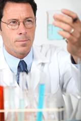 Male scientist holding glass beaker