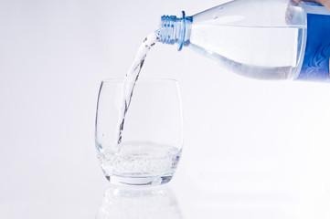 Wasserflasche beim Eingießen von Wasser in ein Glas