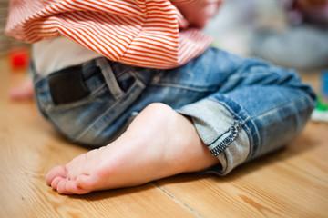 Kind kauert auf Holzboden