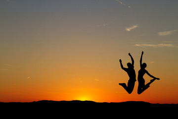 couple jumping in sunset