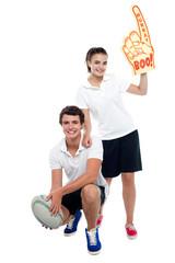 Cheerleader fan girl posing with football team player