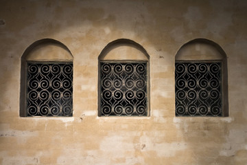 Old wall with three ancient windows background texture
