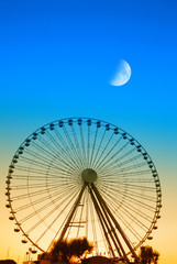 ferris wheel in the evening with moon in the sky