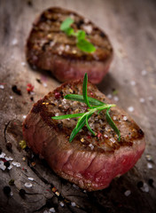 Grilled bbq steaks on wooden background