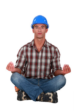 A male construction worker in a yoga position.