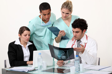 young physician surrounded by male and female nurse