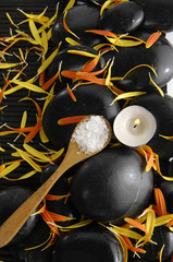 Salt in wooden spoon with flower petals and candle