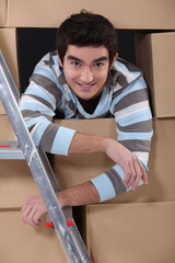 Lad surrounded by cardboard boxes