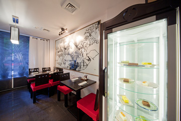 Sushi Restaurant with chairs and refrigerator with cakes, indoor